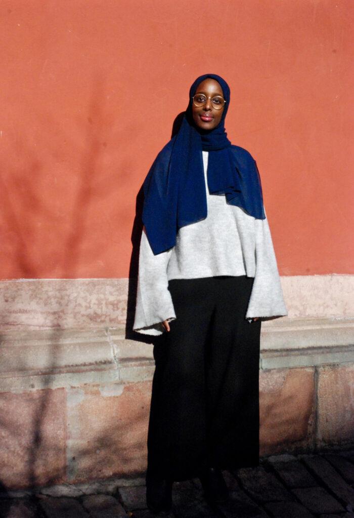 Poeten Mona Monasar i helfigur framför en husvägg.