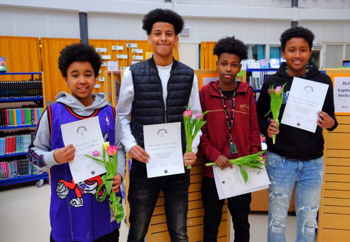 Fyra pojkar med diplom och blommor står i ett bibliotek.